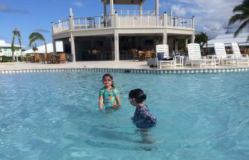 At the Cayman Brac Beach Resort, young children play in the shallow end of the free-form pool