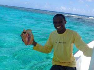 2016 DoE intern Lorenzo Currie assisting with the department's annual conch survey